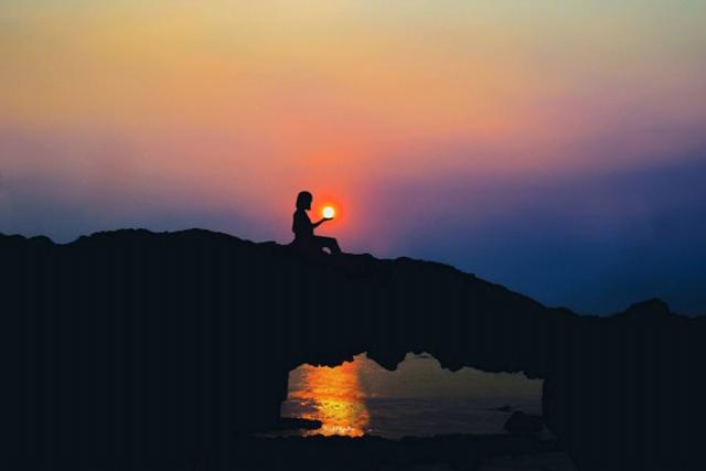 Mặt trời như một hòn lửa trên tay cô gái